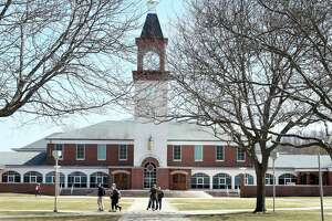Students walk past the Arnold Bernhard Library at Quinnipiac University in Hamden on March 28, 2019.
