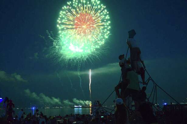 Skyrockets light up the sky over Long Island Sound at the Independence Day Fireworks Fundraising Show at Compo Beach, Monday, July 3, 2017 in Westport, Conn.