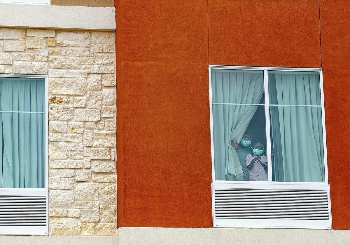 An asylum-seeking Haitian mother and her 3-year-old daughter on Wednesday look out the window of the room at a Homewood Suites by Hilton near the San Antonio airport where they are being held by ICE.