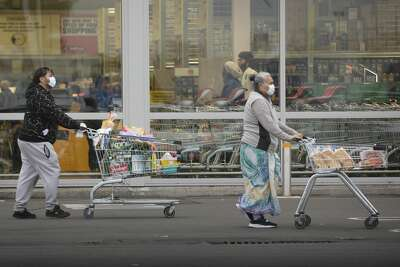 People wearing face masks, pushe shopping cart with their groceryitemsin Christchurch, New Zealand, on April 01, 2020.New Zealand has been lockdown for four weeksin an attempt to minimize the spread of the Covid-19 virus since the 25th of March. There are currently 708 cases of COVID-19 in New Zealand and one person died as a result of the virus. (Photo by Sanka Vidanagama/NurPhoto via Getty Images)
