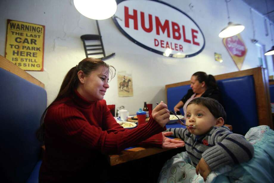 Lourdes Figueroa feeds grandson Maison Aguirre at Tom Ott's Humble City Cafe, on Thursday, Nov. 13, 2014, in Humble. Humble residents are trying to preserve the identity of Old Humble as a small town in the midst of the development all around it. ( Mayra Beltran / Houston Chronicle ) Photo: Mayra Beltran, Staff / Houston Chronicle / © 2014 Houston Chronicle