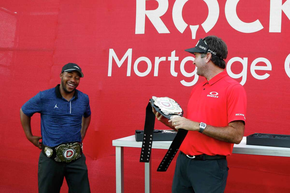 Harold Varner III, left, and Bubba Watson show off the winner's belts after their win in a nine-hole exhibition against Jason Day and Wesley Bryan ahead of the Rocket Mortgage Classic golf tournament, Wednesday, July 1, 2020, at the Detroit Golf Club in Detroit. (AP Photo/Carlos Osorio)