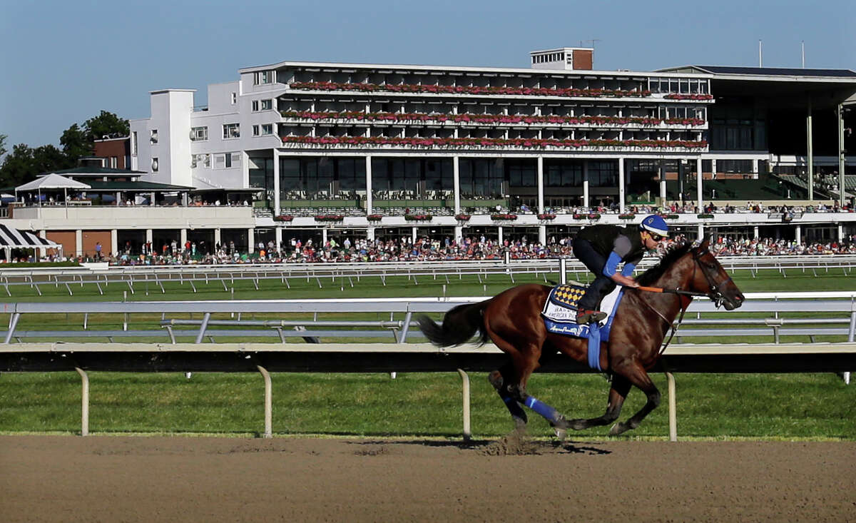 FILE - In this July 31, 2015, file photo, people watch as Triple Crown winner American Pharoah with Jorge Alvarez up trains at Monmouth Park in Oceanport, N.J. With the opening of the thoroughbred season at Monmouth Park just days away, chief executive Dennis Drazin knows the track will be beating the odds by just breaking even. The coronavirus pandemic has idled the New Jersey Shore track for two months. (AP Photo/Mel Evans, File)