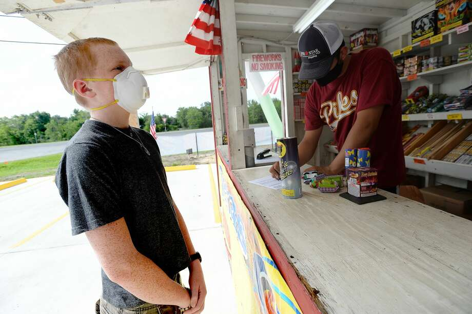 David Reyna helps Alexander Huff decide on fireworks to purchase as he and Claudia Cannon work the Ramirez fireworks stand Wednesday. The stand opened Monday, and Reyna says the early business has been higher than in years past, when they typically remain slow until a day or two before the Fourth of July. He anticipates it will pick up even more in the coming days, especially as several cities have canceled annual fireworks celebrations or significantly changed them due to COVID-19 safety concerns. Photo taken Wednesday, July 1, 2020 Kim Brent/The Enterprise Photo: Kim Brent/The Enterprise
