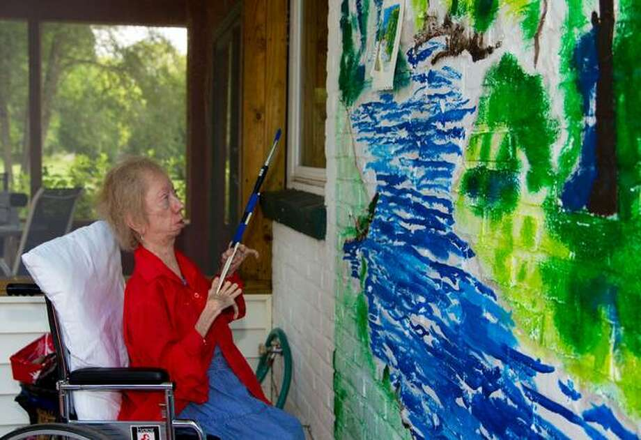 Vicki Conley, 70, of Godfrey, painting a mural. When Conley was 6 years old, she became ill with what she described as a muscular dystrophy-type of disease — dermatomyositis — believed to be genetic. She recovered that first time, and attended school until a second flare up of the same disease, while in eighth grade, prompted the need for home schooling. At this time, Conley took up drawing and painting. Photo: For The Telegraph