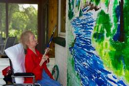 Vicki Conley, 70, of Godfrey, painting a mural. When Conley was 6 years old, she became ill with what she described as a muscular dystrophy-type of disease - dermatomyositis - believed to be genetic. She recovered that first time, and attended school until a second flare up of the same disease, while in eighth grade, prompted the need for home schooling. At this time, Conley took up drawing and painting.