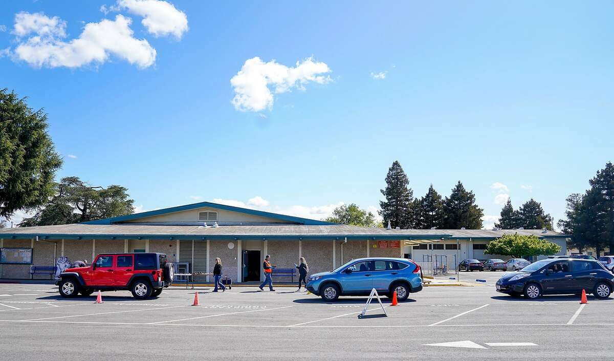 Parents wait in their car as they pick up Chromebooks at Laurelwood Elementary school so their children can use them at home to attend online classes in the Santa Clara Unified District during the coronavirus outbreak on Thursday, March 26, 2020, in Santa Clara, Calif.