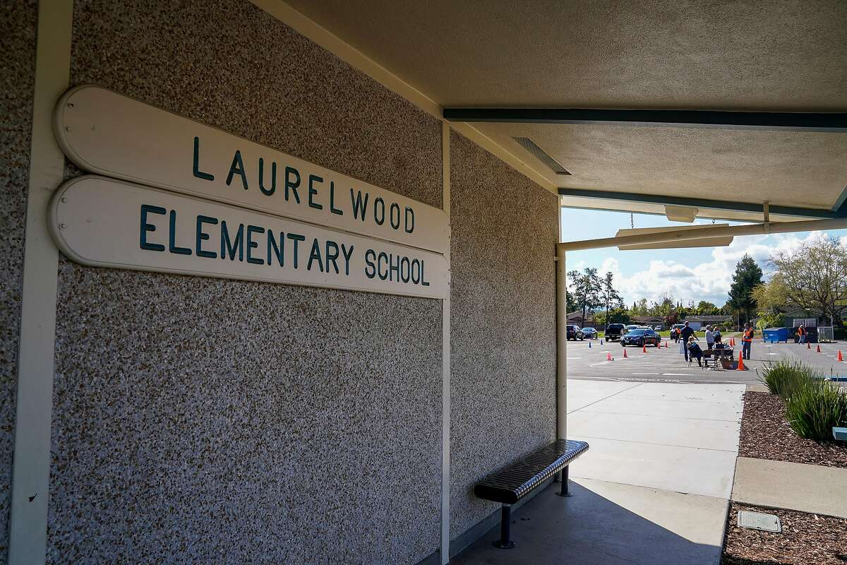 Volunteers at Laurelwood Elementary school handed out Chromebooks to parents at a drive through so students can use them at home to attend online classes in the Santa Clara Unified District during the coronavirus outbreak on Thursday, March 26, 2020, in Santa Clara, Calif.
