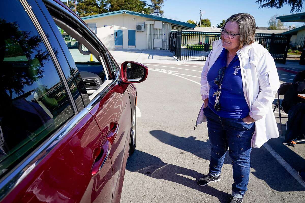 Lori Roger, principal at Laurelwood Elementary school, talks to a parent they pick up a Chromebook at a drive through so students can use them at home to attend online classes in the Santa Clara Unified District during the coronavirus outbreak on Thursday, March 26, 2020, in Santa Clara, Calif.