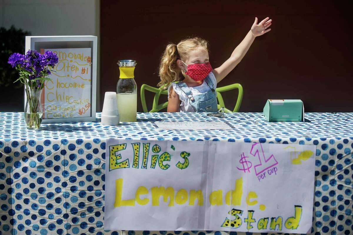 Ellie Martindale, 6, demonstrates Wednesday how she waves down passersby from her driveway while working her lemonade stand, which raised $250 for flood relief. For more photos, visit www.ourmidland.com. (Katy Kildee/kkildee@mdn.net)