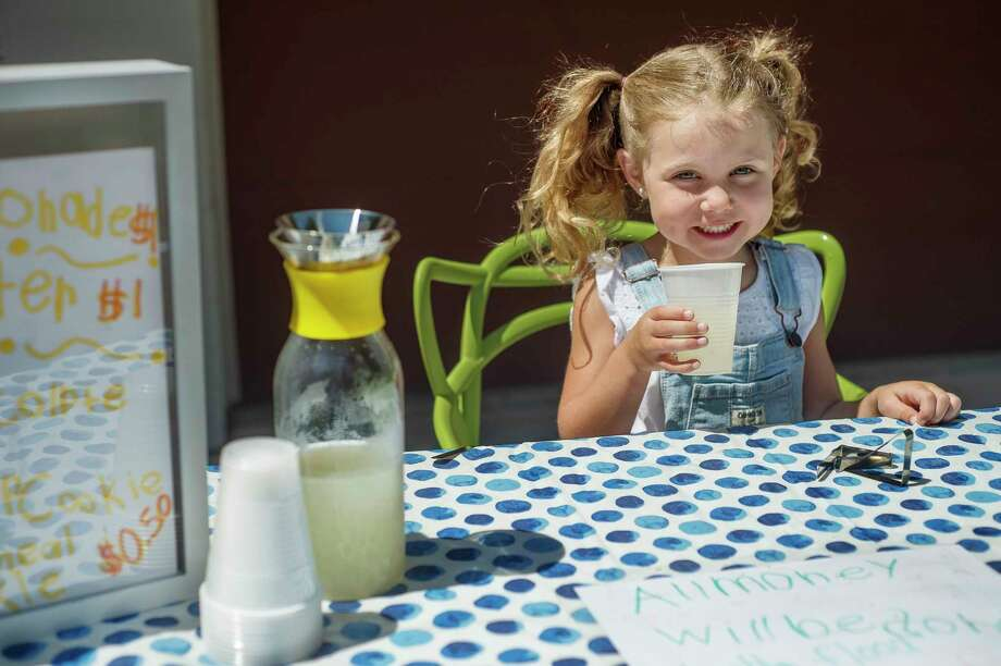 Ellie Martindale, 6, takes a sip of lemonade at her lemonade stand Wednesday, which raised $250 for flood relief. (Katy Kildee/kkildee@mdn.net)