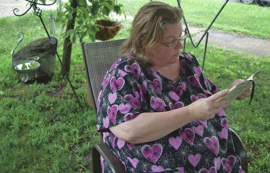 Tracey Hart-Miller of Jacksonville reads a book in her yard. Hart-Miller said the pandemic has made her appreciate solitary activities such as reading since she is unable to go out for entertainment. Photo: Marco Cartolano | Journal-Courier
