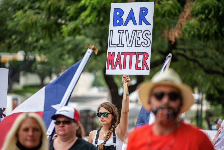 """A demonstrator holds up a sign during a """"Bar Lives Matter"""" protest in Austin, Texas, on June 30, 2020. Photo: Bloomberg Photo By Sergio Flores / © 2020 Bloomberg Finance LP"""