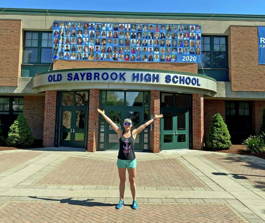 Elayne Marineau poses in front of Old Saybrook High School 2 miles shy of completing 123 miles - 1 mile for each graduate in the class of 2020. Photo: Contributed