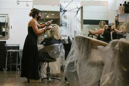 Dulce Astolfi, left, owner and colorist at Sorelle Hair Studio in Maple Glen, Pa., applies hair color to her client, Beth Dickson, on Friday, the first day the salon was allowed to reopen.