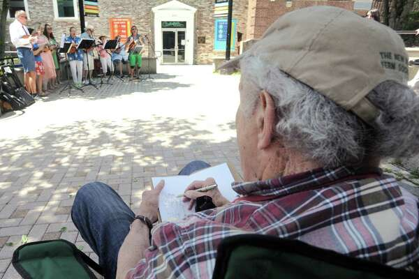 Westport artist Dick Rauh sketches The Cukes as they perform outside the Downtown Cabaret Theater as part Make Music Day Bridgeport on Thursday, June 21, 2018. Free musical events were held at several downtown locations, starting at noon and continuing into the evening, including performances at the historic Bijou Theatre. Make Music Day is held in more than 800 cities in 120 countries to mark the summer solstice. City Lights/Bridgeport Art Trail is the lead organization of Make Music Day Bridgeport