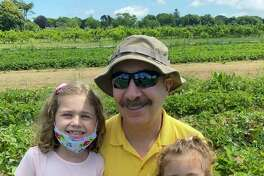 Chloe, left, and Lilly help grandpa Jerry Zezima find the best strawberries in the field.