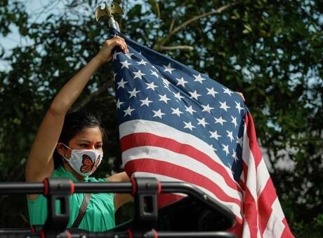 Immigrant rights activist Flor Hoill wears a face mask as she places an American flag atop of vehicle in front of the Joe Corley Detention Facility, Friday, May 29, 2020, in Conroe.