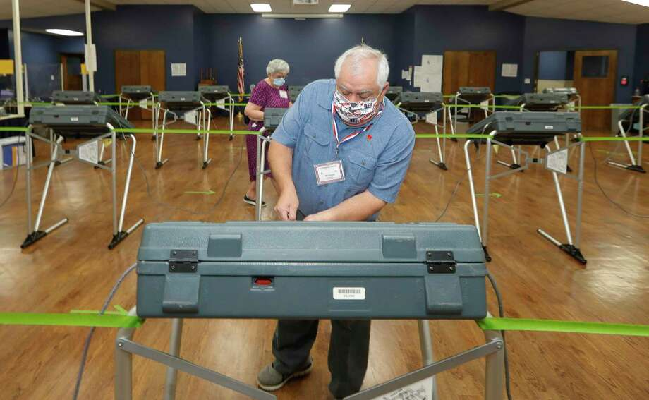 Michael Trahan wears a facemask as he unlocks voting stations before the polls open at the South Montgomery County Community Center, Thursday, July 2, 2020, in The Woodlands. Election officials have implemented several safety and sanitization features to protect voters and polling location volunteers from the coronavirus. Photo: Jason Fochtman, Houston Chronicle / Staff Photographer / 2020 © Houston Chronicle