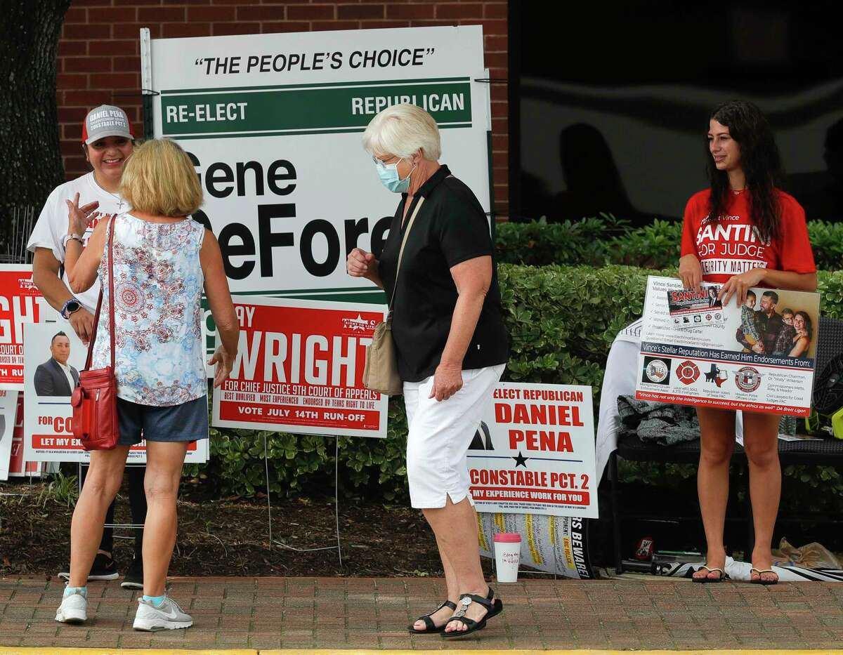 A woman wears a facemask as she walks past political supporters during the second day of early voting at the Lee G. Alworth Building, Tuesday, June 30, 2020, in Conroe. Early voting for the run-off elections for chief justice of the 9th Court of Appeals, Precinct 2 Constable and judge of the newly created 457th state District Court runs through July 10. Election Day is July 14.