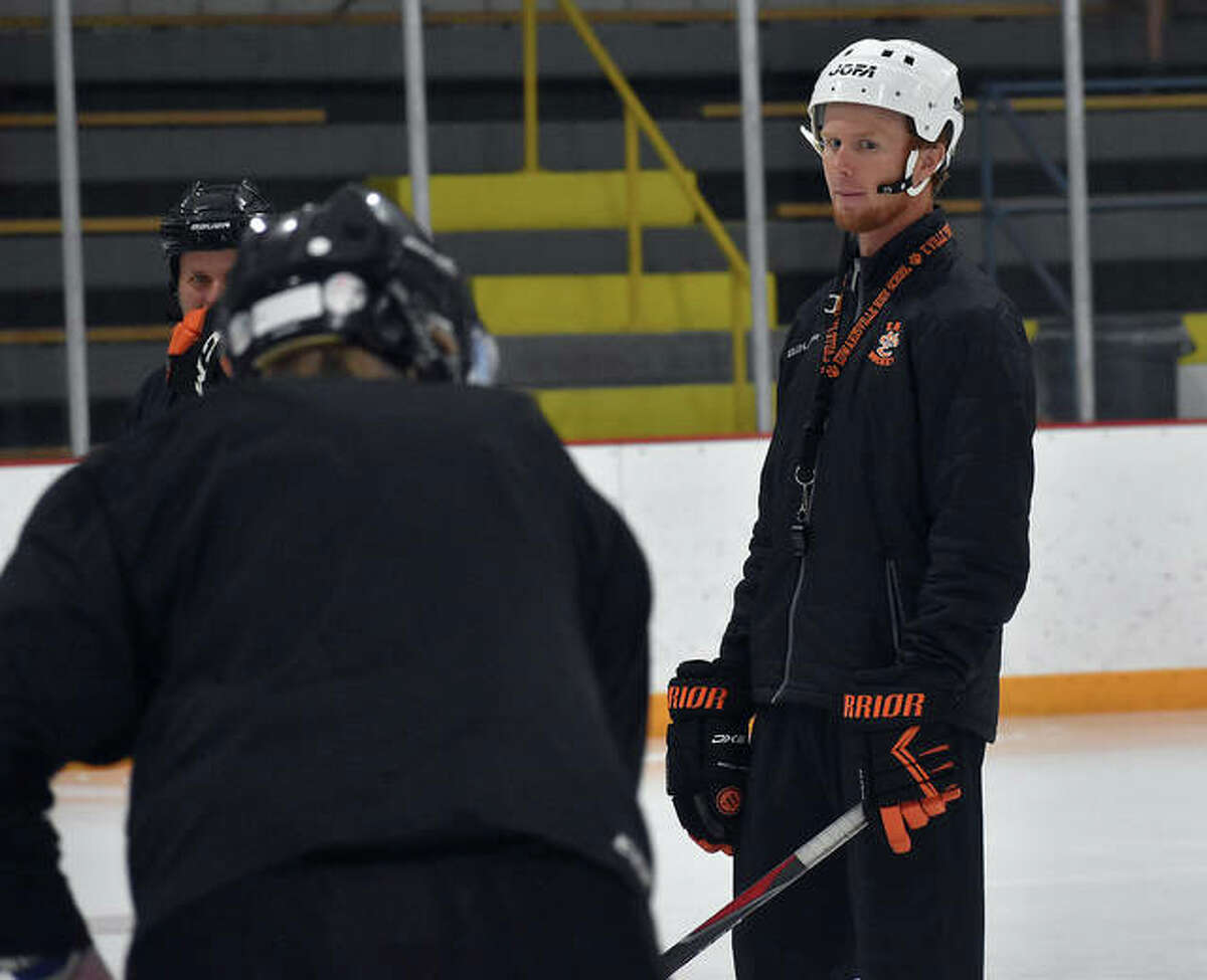 Edwardsville coach Jason Walker watches a skater complete a drill during Wednesday's conditioning session inside the East Alton Ice Arena.