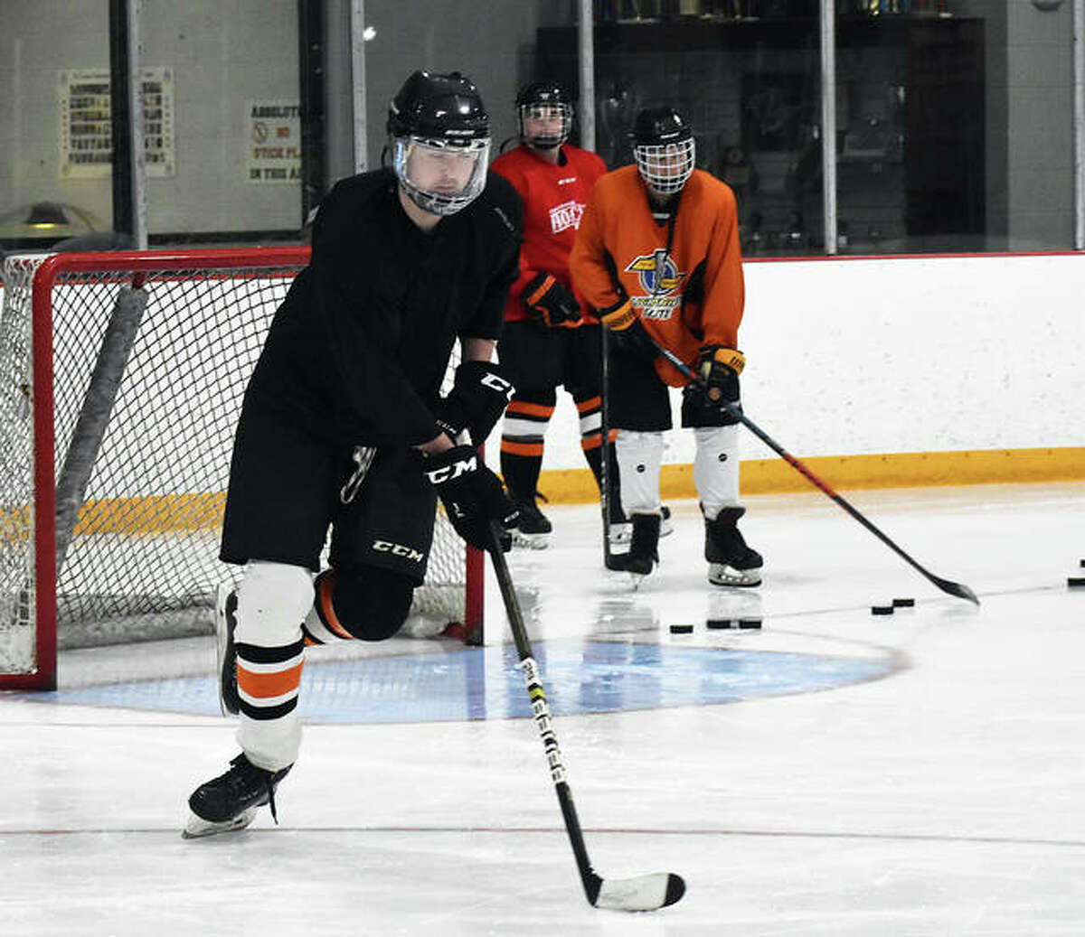 Members of the Edwardsville ice hockey program complete a drill during Wednesday's conditioning session inside the East Alton Ice Arena.