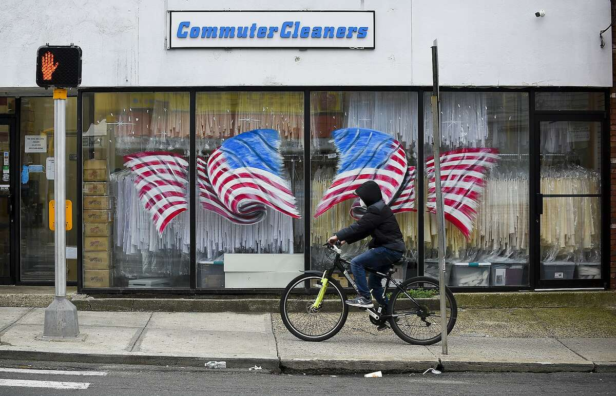 A bicyclist passes in front of American Flags displayed on the windows of Stamford Uniform in Stamford, Connecticut on April 29, 2020. Owner Paul McDonald has seen a dramatic decrease in business as a direct result of the COVID-19 pandemic. The dry cleaning laundry service provides uniform, linen towel, apron and napkin to regional clients in Connecticut and New York.
