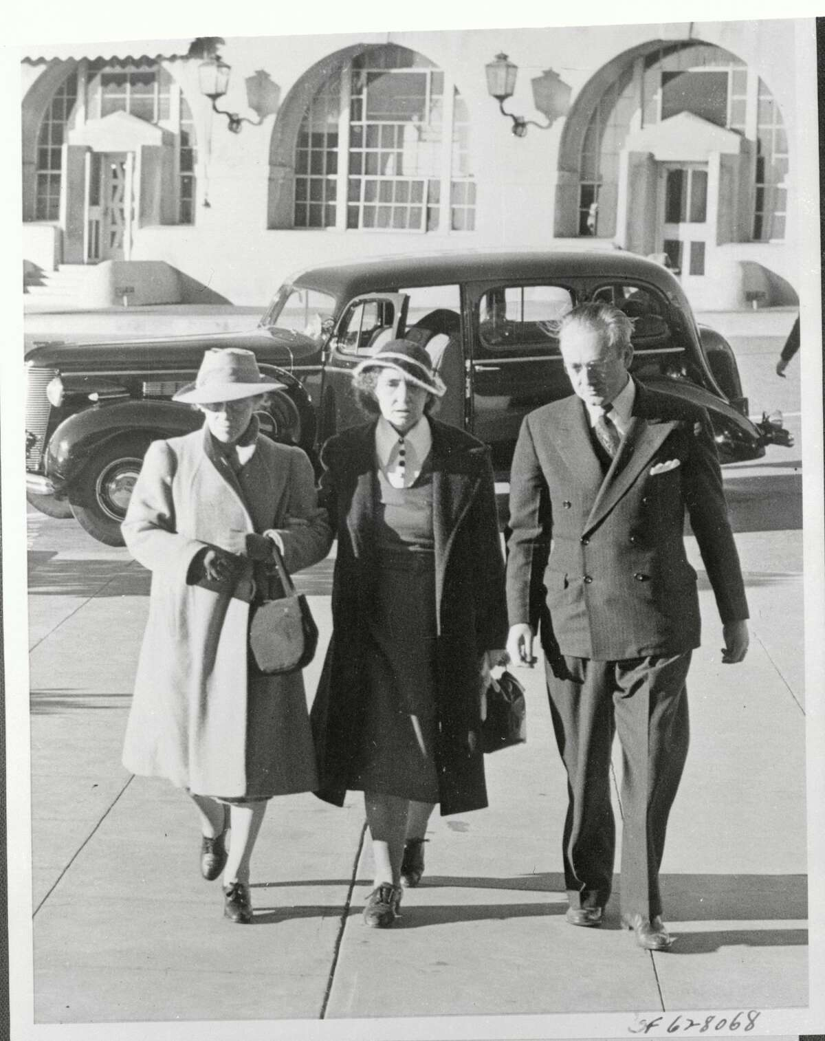Saved from death three times by gubernatorial reprieves, Juanita Spinelli, center, walks into San Quentin prison before her execution, which took place on November 21, 1941. She was the first woman to die in San Quentin's lethal gas chamber. At her left in the picture is the matron, who accompanied her from Tehachapi Woman's Prison, (R), and Warden Clinton Duffy.