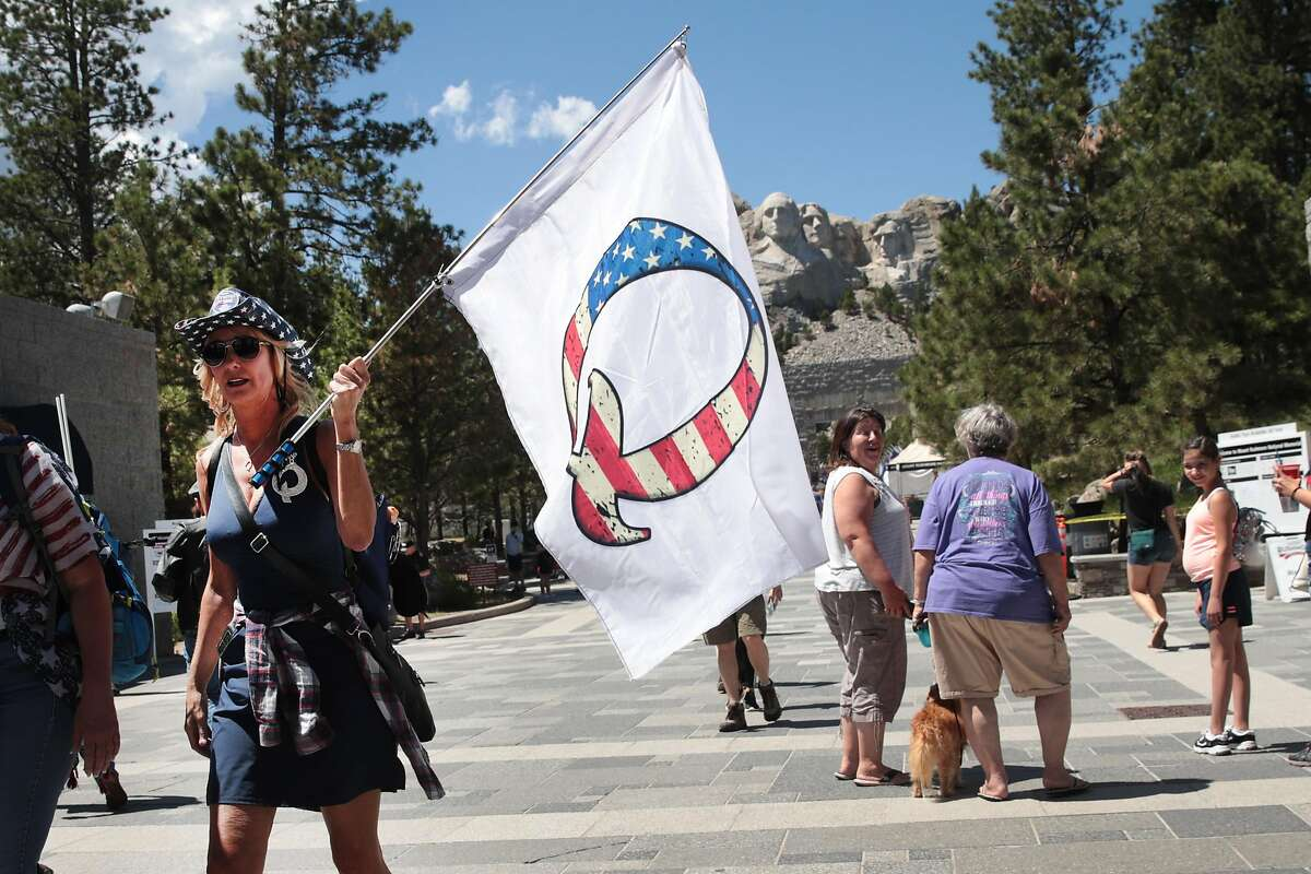 A Donald Trump supporter holding a QAnon flag visits Mount Rushmore National Monument on July 1, 2020, in Keystone, S.D.