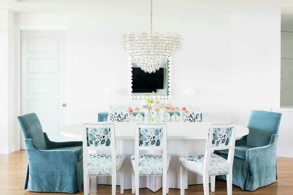 A vintage Italian Murano glass chandelier is a showstopper in the dining area. A white pedestal table is easier to sit at — no one's knees bump the table legs.