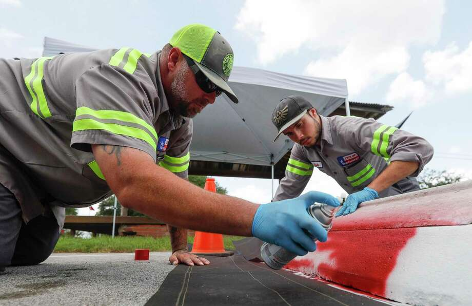 Montgomery public works department employee Ryan Thomas, left, sprays red paint on a parking stop while Jack Brown holds a template as crews repaint one of several parking spots around downtown Montgomery to depict the Texas flag, Wednesday, July 1, 2020, in Montgomery. Charles B. Stewart, a resident of Montgomery in the 1800s, sketched the original design for the state flag. Photo: Jason Fochtman, Houston Chronicle / Staff Photographer / 2020 © Houston Chronicle