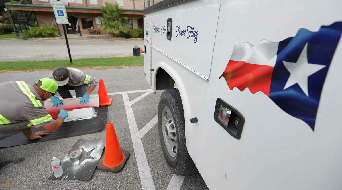 The side of a Montgomery public works department truck is seen as Ryan Thomas, left, sprays red paint on a parking stop while Jack Brown holds a template as crews repaint one of several parking spots around downtown Montgomery to depict the Texas flag, Wednesday, July 1, 2020, in Montgomery. Charles B. Stewart, a resident of Montgomery in the 1800s, sketched the original design for the state flag.
