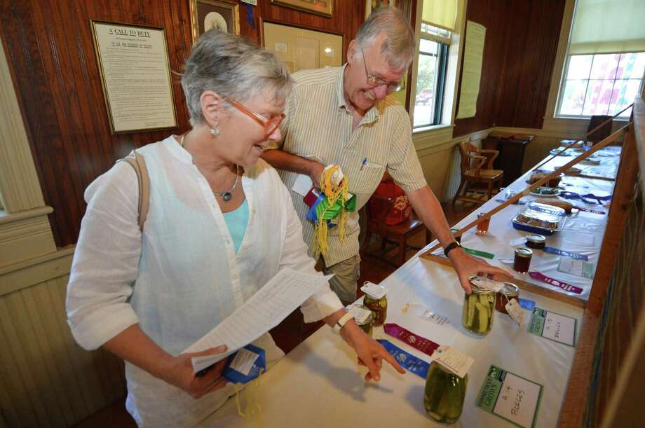 Sara Schrager and Bil Mikulewicz place ribbons on winning entries during judging at the 84th annual Cannon Grange Fair in Wilton in 2016. This year's fair will be held virtually. Photo: File Photo / Connecticut Post