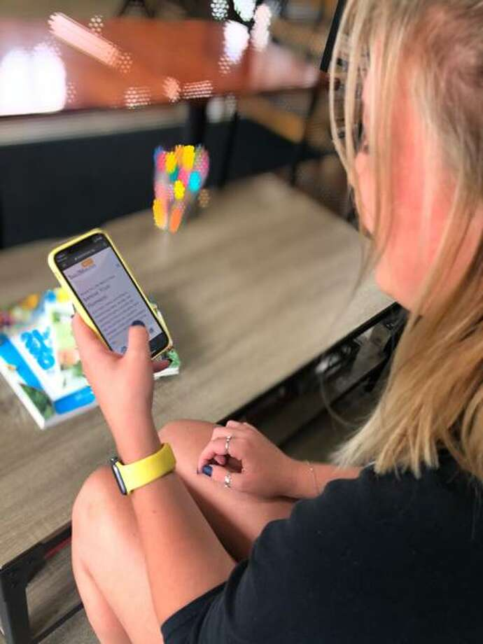 A woman uses her cellphone to read content on Take2Minutes, a free text messaging service designed to provide and positive messages, guided meditations and other activities for users. The idea is the brainchild of Edwardsville native Marc Fussell.