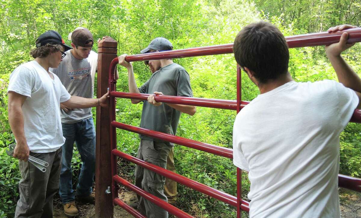 Student volunteers from the New Milford Youth Agency put the finishing touches on a gate to Weantinoge's 80-acre Still Reserve Preserve in New Milford. August 2015