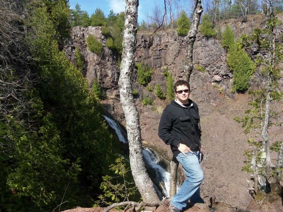 Mitchell Kukulka awkwardly poses in front of a waterfall near Lake Linden in early April 2012. (Photo provided/Emilee Siegrist)