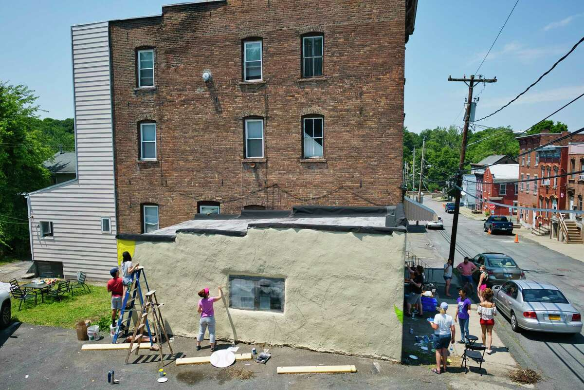 Artist Noreen Powell, third from left, sketches out her mural as others paint the mural on the garage of BunkablRPI.