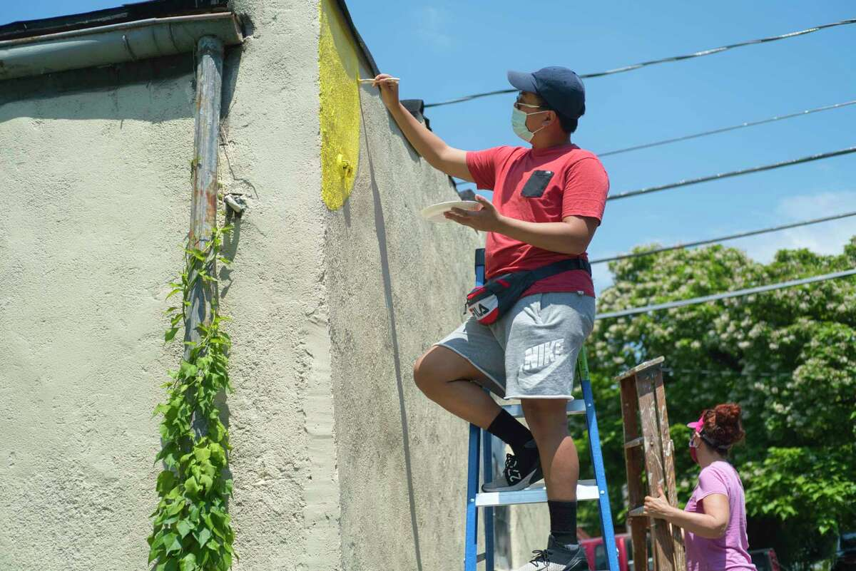 RPI student A.J. Gevero helps to paint the mural on the BunkablRPI garage.