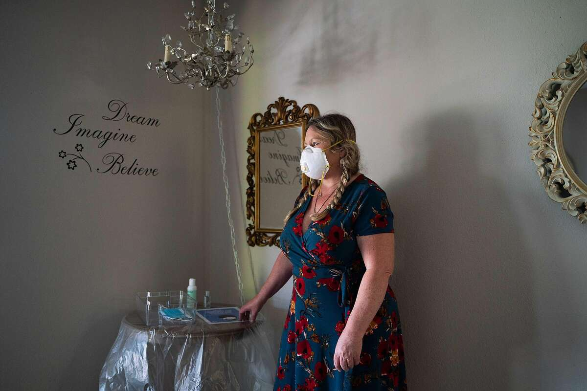 """Tess Vasquez, 58, of Pittsburg, poses for a photo inside of Vitale Physical Therapy and Wellness, where she works as a massage therapist in Pleasant Hill, Calif., on Wednesday, July 1, 2020. """"We want to open so we can help as many people as we can,"""" said Vasquez. """"I work with people from all walks of life and that's why I love what I do. Right now it's my responsibility is to keep everyone safe. I would be devastated if I lost a client."""""""