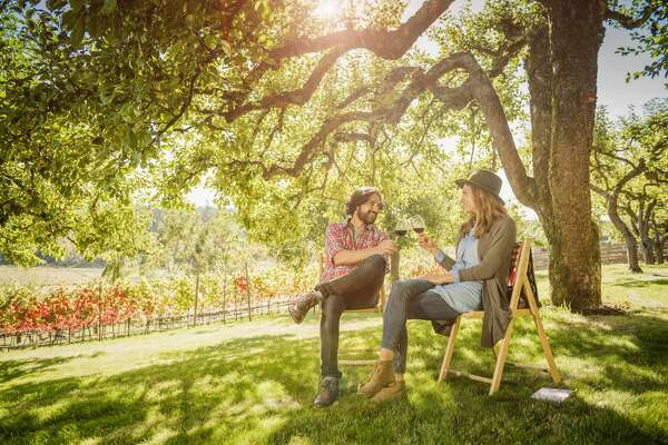Two people drinking wine outside at a vineyard