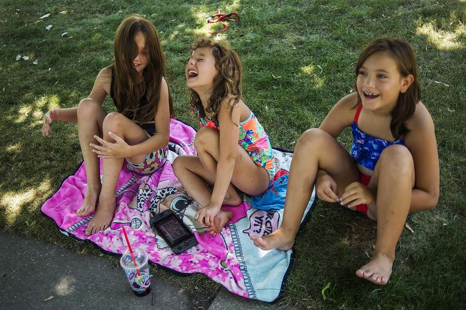 From left, Leah Morningstar, 8, Olivia Gray, 7, and Addison Wentworth, 8, laugh together in Olivia's front yard Thursday, July 2, 2020. (Katy Kildee/kkildee@mdn.net) Photo: (Katy Kildee/kkildee@mdn.net)