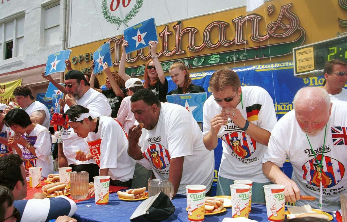 Competitors in the annual Nathan's Famous hot dog eating contest begin eating July 4, 2000 at Nathan's Famous at Coney Island in New York City.