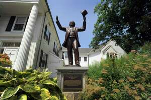 A Statue of P.T.Barnum by sculptor David Gesualdi stands in front of the Bethel Library on Greenwood Avenue in Bethel Thursday, July 12, 2018.