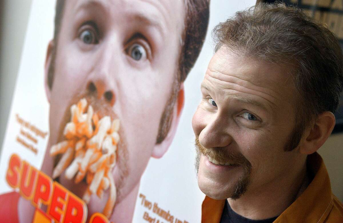 Morgan Spurlock poses in front of the poster for his documentary