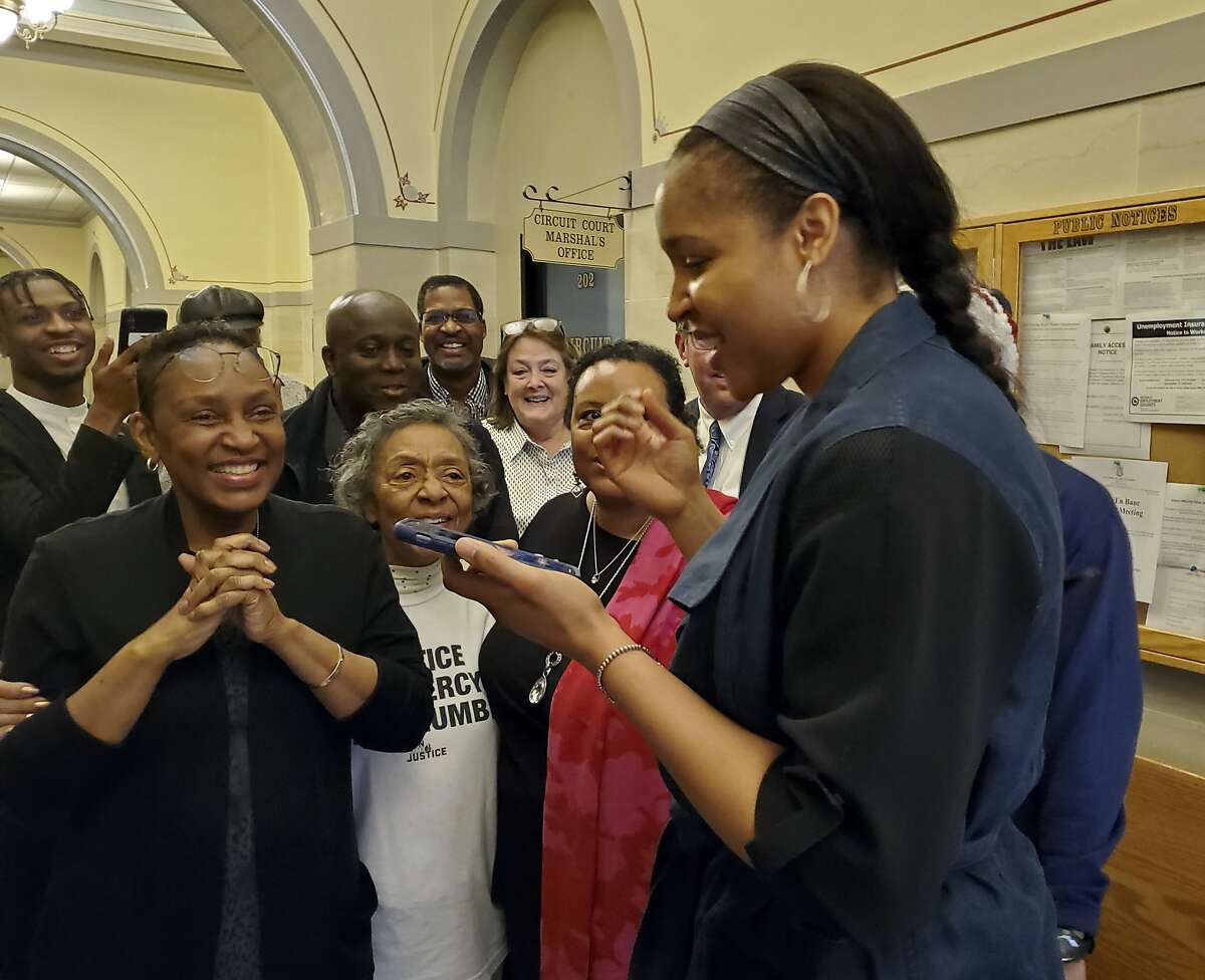FILE - In this Monday, March 9, 2020, file photo, Jefferson City, Mo., native and WNBA star Maya Moore, right, calls Jonathan Irons as supporters react in Jefferson City after Cole County Judge Dan Green overturned Irons' convictions in a 1997 burglary and assault case. Moore, a family friend, had supported Irons, sharing his story on a national basis. Irons was freed from prison Wednesday, July 1, 2020, after a county prosecutor declined to retry his case, punctuating years of work by Moore and other supporters who argued he was falsely convicted of burglary and assault charges. (Jeff Haldiman/The Jefferson City News-Tribune via AP, File)