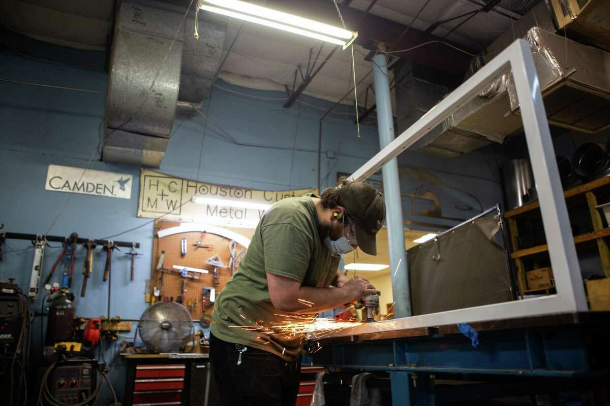 """Shop hand Aaron Block works on a bathroom stall at Houston Custom Metal Works on July 2, 2020. Custom projects for residential and commercial businesses have picked back up but demand for plastic """"sneeze guards"""" remains steady."""