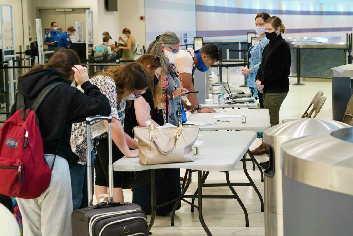 Employees of the New York State Department of Health, right, look on as airline passengers arriving from Florida fill out health screening forms at the Albany International Airport on Thursday, July 2, 2020, in Colonie, N.Y. (Paul Buckowski/Times Union)