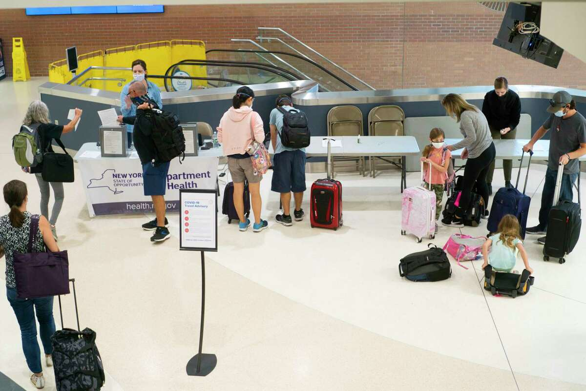 Passengers from a flight from Florida fill out health screening forms to turn them in at a table set up by the New York State Department of Health at the Albany International Airport on Thursday, July 2, 2020, in Colonie, N.Y. (Paul Buckowski/Times Union)