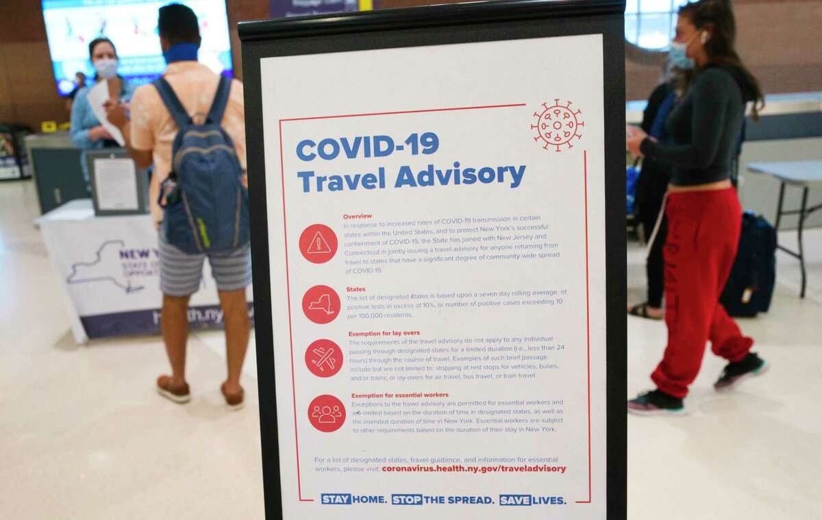 Passengers from a flight from Florida line up to fill out health screening forms to turn in at a table set up by the New York State Department of Health at the Albany International Airport on Thursday, July 2, 2020, in Colonie, N.Y. (Paul Buckowski/Times Union)