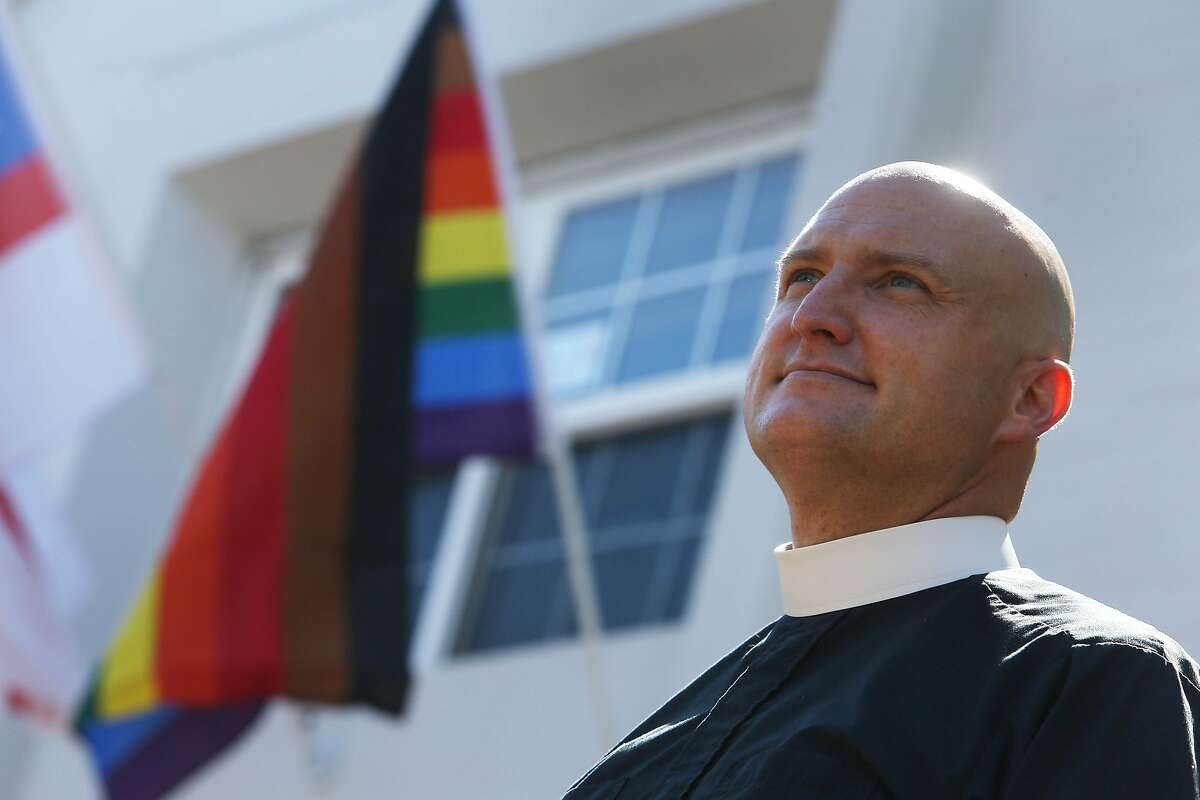 Reverend Alan Gates stands for a portrait at the front of the parish hall at Episcopal Church of the Epiphany next to a Philadelphia Pride flag on Wednesday, July 1, 2020 in San Carlos, Calif.